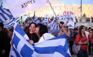 """""""No'' supporters wave a Greek flag in celebration at  Syntagma Square in Athens, Greece after more than 61 percent of Greeks voted """"no"""" to creditors' demands in the referendum on Jul. 5, 2015."""